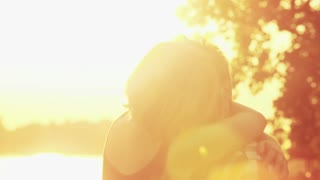 Cute young couple kissing and laughing at sunset, graded.