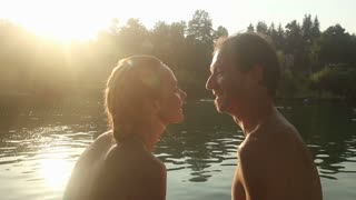 Cute young couple kissing and laughing at sunset