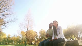 Cute young couple listening to music on headphones while hanging out in park, graded
