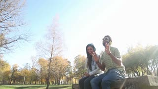 Cute young couple listening to music on headphones while hanging out in park