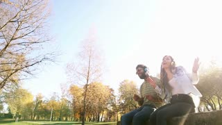 Cute young couple listening to music on headphones while sitting at the park, graded