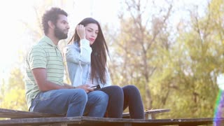 Cute young couple sitting on bench and listening to music on shared earphones on beautiful sunny day, graded