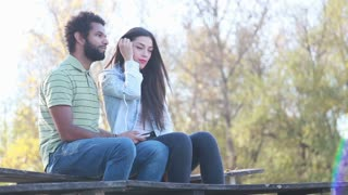 Cute young couple sitting on bench and listening to music on shared earphones on beautiful sunny day