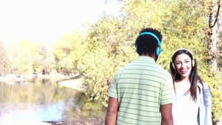 Cute young couple with headphones listening to music and dancing by the lake on a beautiful autumn day, graded