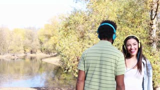 Cute young couple with headphones listening to music and dancing by the lake on a beautiful autumn day