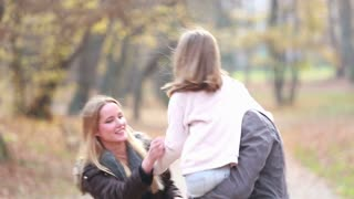 Cute young family having fun in park, father carries daughter in his arms