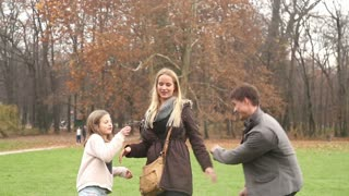Cute young girl playing with her parents in park in autumn