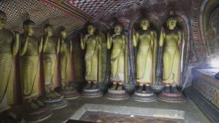 DAMBULLA, SRI LANKA - FEBRUARY 2014: The view of standing Buddhas at the Golden Temple of Dambulla. The Golden Temple of Dambulla is a World Heritage Site in Sri Lanka.