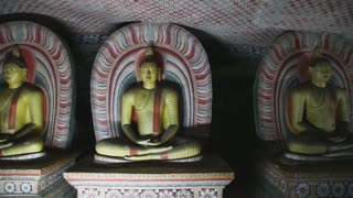 DAMBULLA, SRI LANKA - FEBRUARY 2014: The view of three sitting Buddhas at the Golden Temple of Dambulla. The Golden Temple of Dambulla is a World Heritage Site in Sri Lanka.