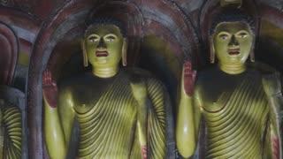 DAMBULLA, SRI LANKA - FEBRUARY 2014: The view of three standing Buddhas at the Golden Temple of Dambulla. The Golden Temple of Dambulla is a World Heritage Site in Sri Lanka.