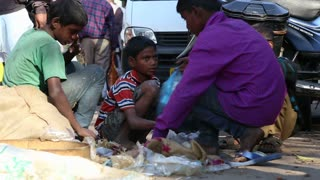 DELHI, INDIA - 4 MARCH 2015: Group of children packing stuff in bag at street in Delhi.