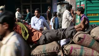 DELHI, INDIA - 4 MARCH 2015: Man sleeping at pile of sacks, with people passing by him at street in Delhi.