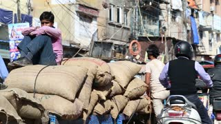 DELHI, INDIA - 4 MARCH 2015: Men by pile of large sacks, with people passing by them.