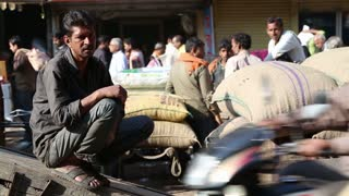 DELHI, INDIA - 4 MARCH 2015: Portrait of Indian man sitting by pile of sacks while people pass by.
