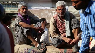 DELHI, INDIA - 4 MARCH 2015: Portrait of two men sitting at sack, with people passing in front.