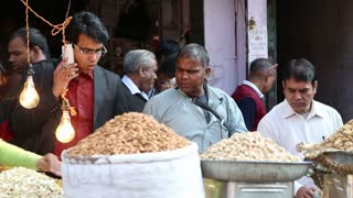 DELHI, INDIA - 4 MARCH 2015: Three Indian men by street stand with seeds at market in Delhi.