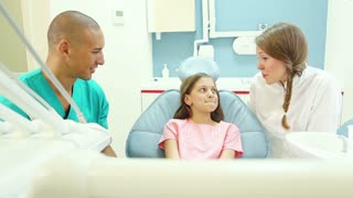 Dental assistant and dentist showing mouth mirror to little girl before check up