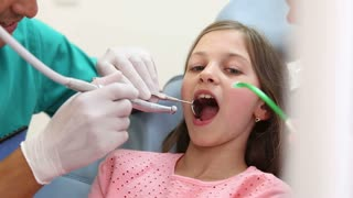 Dentist and assistant fixing teeth of cute girl, she's showing thumbs up