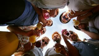 Eight multi-ethnic friends looking down at camera and toasting