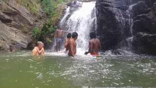 ELLA, SRI LANKA - MARCH 2014: Slow motion of relaxed people standing in the river in front of waterfall.