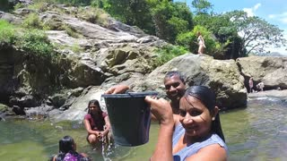 ELLA, SRI LANKA - MARCH 2014: Woman standing in the river pours water from the bucket on herself