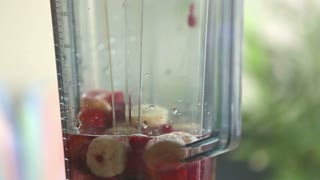 Extreme close-up of blending fruits in blender, in slow motion, graded