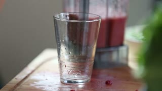 Extreme close-up of pouring fruit smoothie into drinking glass, in slow motion