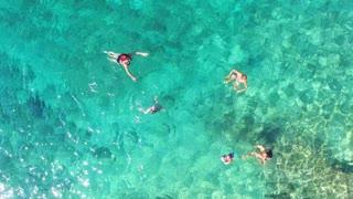 Family having fun swimming in turquoise sea