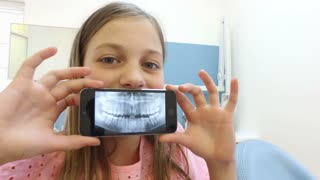 Father and daughter having fun playing with dental X- ray photo at dentist