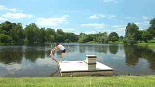 Father playing with daughter on floating platform on lake in France
