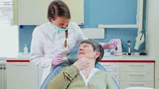 Female dentist doing dental treatment to elderly patient