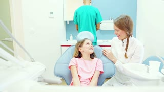 Female dentist talks with young patient, assistant does routine check up