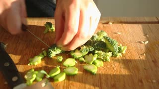 Female hands cutting vegetables on wooden board