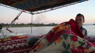 Female tourist covered with blanket on felucca at sunset
