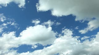 Fluffy clouds moving slowly on blue sky over highway