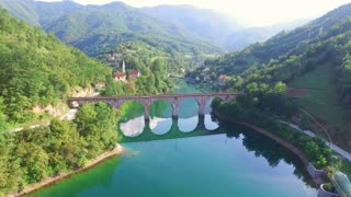 Flying over river and old stone bridge in Bosnia
