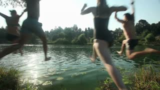Four young friends having fun jumping into river at sunset, slow motion