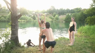 Four young happy friends having fun jumping off rope swing into river at sunset, graded, in slow motion