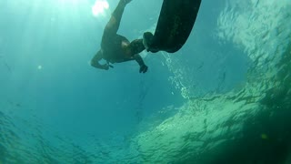 free diver swimming underwater in apnea