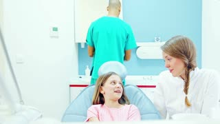 Friendly dentist talks with young patient while assistant examines her
