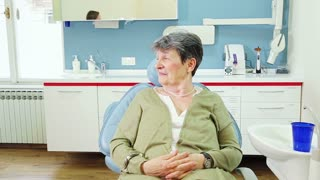 Friendly elderly woman with toothache at dentist