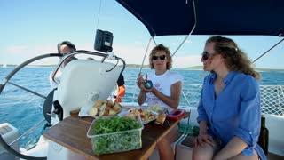 Friends enjoying food on board sailboat at sea