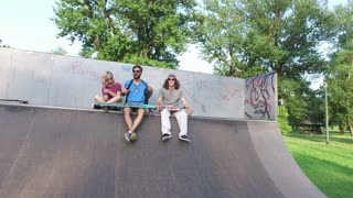 Friends sitting on a ramp at skatepark and chilling