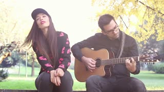 Front view of handsome young man playing guitar while beautiful woman sitting next to him on park bench, graded, in slow motion