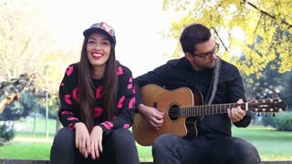 Front view of handsome young man playing guitar while beautiful woman sitting next to him on park bench