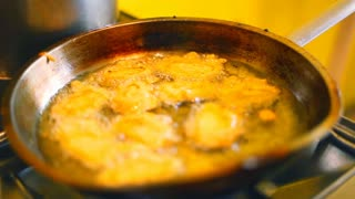 Frying hot sizzling oil food in pan on stove
