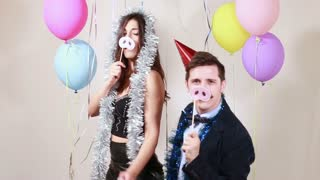 Fun crazy couple playing with props in photo booth