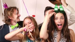 Funny couples playing with props in party photo booth