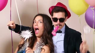 Funny crazy couple having fun in photo booth