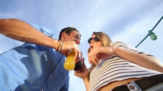 Funny drunk couple looking down at camera, drinking cocktails and laughing